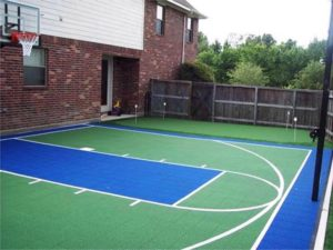 Green and blue, in-home basketball court with a fence and brick wall.